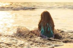 Pequeña muchacha asiática que juega y que se divierte en el mar en la puesta del sol fotografía de archivo libre de regalías