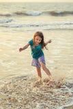 Pequeña muchacha asiática que juega y que se divierte en el mar en la puesta del sol fotos de archivo libres de regalías