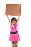 Pequeña muchacha asiática que lleva a cabo al tablero blanco Fotos de archivo libres de regalías