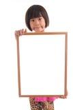 Pequeña muchacha asiática que lleva a cabo al tablero blanco Imágenes de archivo libres de regalías