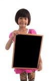 Pequeña muchacha asiática que lleva a cabo al tablero negro Foto de archivo