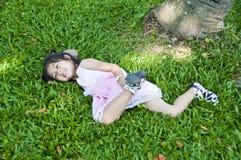 Pequeña muchacha asiática que miente en hierba verde. Imagen de archivo libre de regalías