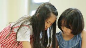 Pequeña muchacha asiática que mira Asia sudoriental para el rompecabezas del juego en un mapa geográfico almacen de metraje de vídeo