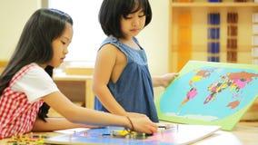 Pequeña muchacha asiática que mira Asia sudoriental para el rompecabezas del juego en un mapa geográfico metrajes
