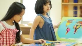 Pequeña muchacha asiática que mira Asia sudoriental para el rompecabezas del juego en un mapa geográfico almacen de video