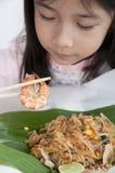 Pequeña muchacha asiática que mira un camarón. Fotos de archivo