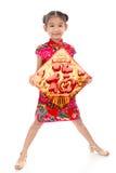 Pequeña muchacha asiática que muestra saludos chinos del Año Nuevo Fotos de archivo libres de regalías