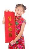 Pequeña muchacha asiática que muestra saludos chinos del Año Nuevo Fotos de archivo