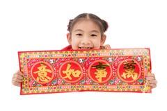 Pequeña muchacha asiática que muestra saludos chinos del Año Nuevo Imagenes de archivo