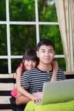 Pequeña muchacha asiática que señala en el ordenador portátil con el hermano mayor Foto de archivo libre de regalías