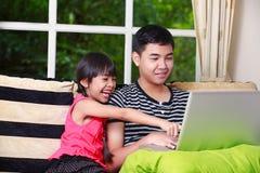 Pequeña muchacha asiática que señala en el ordenador portátil con el hermano mayor Fotos de archivo libres de regalías