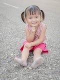 Pequeña muchacha asiática que se sienta y que sonríe en el piso Imagen de archivo libre de regalías