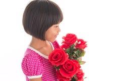 Pequeña muchacha asiática que sostiene una rosa Foto de archivo libre de regalías