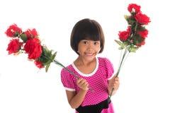 Pequeña muchacha asiática que sostiene una rosa Fotos de archivo