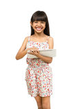 Pequeña muchacha asiática que usa el ordenador de la tableta de la pantalla táctil Foto de archivo