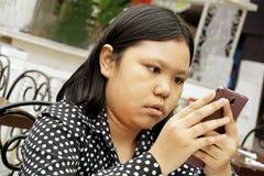 Pequeña muchacha asiática que usa smartphone Imagen de archivo