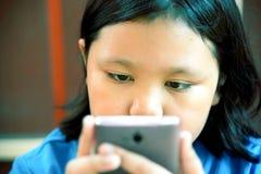 Pequeña muchacha asiática que usa smartphone Fotos de archivo libres de regalías
