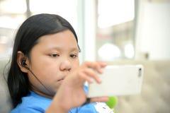 Pequeña muchacha asiática que usa smartphone Imagen de archivo libre de regalías