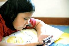 Pequeña muchacha asiática que usa smartphone Fotografía de archivo libre de regalías