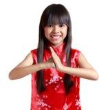 Pequeña muchacha asiática sonriente con el cheongsam que respeta en n china Foto de archivo libre de regalías