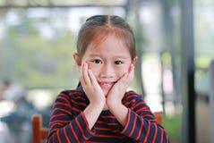 Pequeña muchacha asiática sonriente del niño con el tacto de su mejilla que mira derecho la cámara que se sienta en el café foto de archivo
