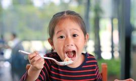 Pequeña muchacha asiática sonriente del niño que se sienta en el café y que come la comida con la mirada derecho imagen de archivo libre de regalías