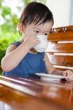 Pequeña muchacha asiática (tailandesa) que bebe de una taza imagen de archivo