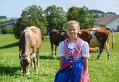 Pequeña muchacha bávara adorable en un campo del país con la vaca en GE Fotografía de archivo libre de regalías