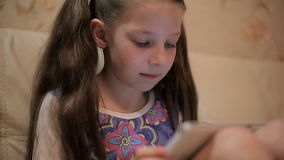 Pequeña muchacha bonita con una tableta en un sofá en casa almacen de video