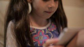Pequeña muchacha bonita con una tableta en un sofá en casa almacen de metraje de vídeo