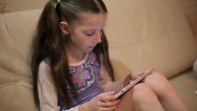Pequeña muchacha bonita con una tableta en un sofá en casa metrajes