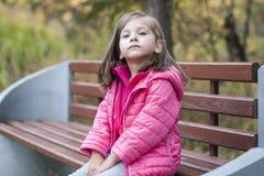 Pequeña muchacha bonita en una capa rosada que se sienta en un banco de madera en el parque en otoño Retrato emocional foto de archivo libre de regalías