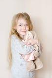 Pequeña muchacha bonita que abraza su conejo del juguete Fotografía de archivo