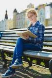 Pequeña muchacha bonita que lee un libro y que se sienta en el banco al aire libre Imágenes de archivo libres de regalías