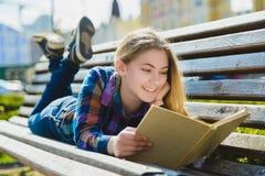 Pequeña muchacha bonita que lee un libro y que se sienta en el banco al aire libre Foto de archivo