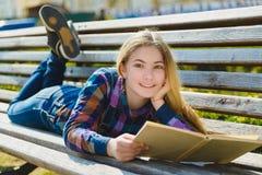 Pequeña muchacha bonita que lee un libro y que se sienta en el banco al aire libre Fotos de archivo
