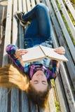Pequeña muchacha bonita que lee un libro y que se sienta en el banco al aire libre Fotografía de archivo libre de regalías