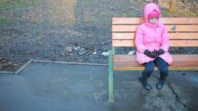 Pequeña muchacha bonita que se sienta en un banco y triste en el parque en otoño almacen de video