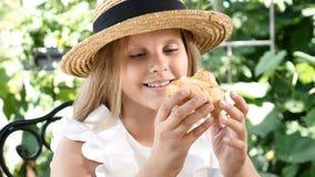 Pequeña muchacha bonita que se sienta en un café de la calle que goza de la torta Sonrisa Disfrute del concepto de la comida 4K almacen de metraje de vídeo