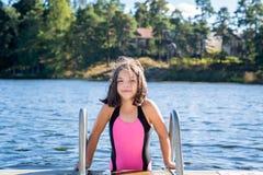 Pequeña muchacha cabelluda marrón linda en el traje de baño alrededor a subir abajo en el agua para nadar Foto de archivo