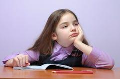 Pequeña muchacha cansada de la escuela que hace homeworks en el escritorio Fotos de archivo libres de regalías