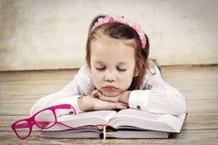 Pequeña muchacha cansada que duerme en los libros foto de archivo libre de regalías