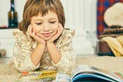 Pequeña muchacha caucásica de Smilling que miente en el piso y que lee un libro ilustrado foto de archivo