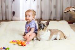 Pequeña muchacha caucásica divertida que el niño se sienta en casa en el piso en una alfombra ligera con el mejor amigo del perro imagen de archivo