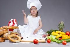 Pequeña muchacha caucásica en el cocinero Uniform Making Dishes Foto de archivo