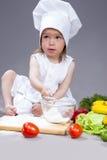 Pequeña muchacha caucásica en el cocinero Uniform Making Dishes en estudio Imagen de archivo