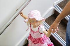 Pequeña muchacha caucásica encantadora en el vestido de flores rosado que mira para arriba, caminando abajo Fotos de archivo