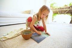 Pequeña muchacha caucásica linda que dibuja en casa Foto de archivo