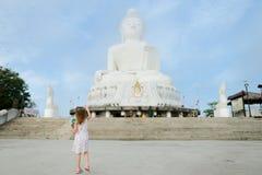 Pequeña muchacha caucásica que mira la estatua blanca de Buda en Phuket Foto de archivo libre de regalías