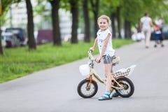 Pequeña muchacha caucásica que monta una bicicleta Foto de archivo
